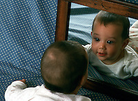 A baby is fascinated, playing with its image in a mirror.