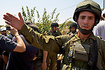 An Israeli soldier tries to prevent members of the press from documenting events during a non-violent demonstration in the West Bank village of Beit Ummar near Hebron on 10/07/2010.