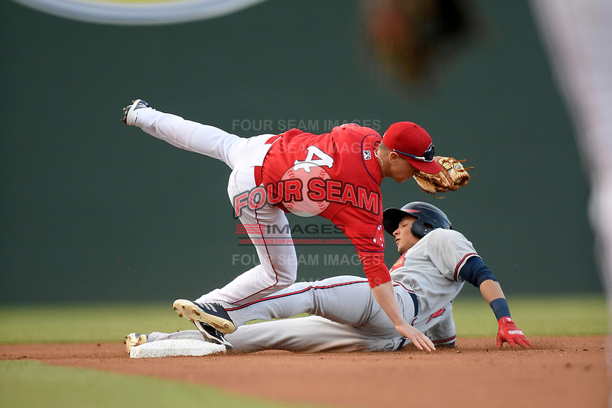 Shortstop Grant Williams (4) of the Greenville Drive tumbles as he makes the tag as Jose Bermudez (7) of the Rome Braves is caught stealing in a game on Saturday, April 20, 2019, at Fluor Field at the West End in Greenville, South Carolina. Rome won, 5-4. (Tom Priddy/Four Seam Images)