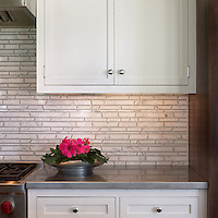 This custom kitchen features a handmade Bamboo mosaic backsplash shown in Bardiglio and Calacatta Tia from New Ravenna.<br />