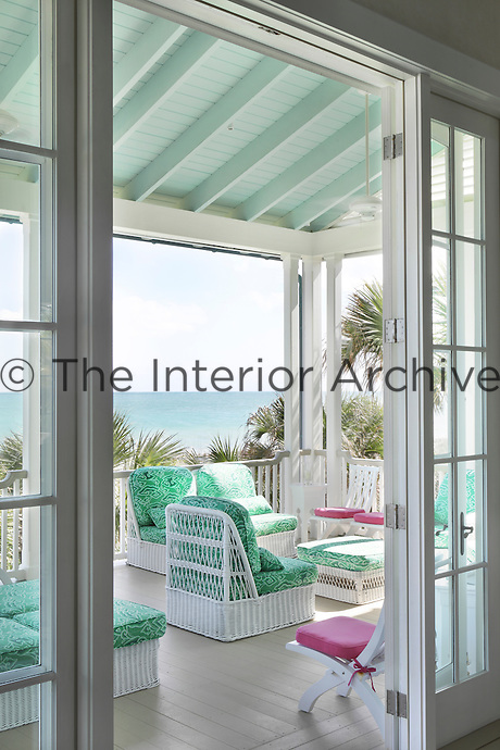 French windows lead onto a covered terrace surrounded by palm trees and views of the sea