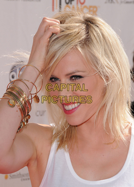 NATASHA BEDINGFIELD .at Stand Up to Cancer held at Sony Picture Studios in Culver City, California, USA, September 10th 2010.     .portrait headshot make-up smiling   white hand touching hair head gold bracelets .CAP/RKE/DVS.©DVS/RockinExposures/Capital Pictures.