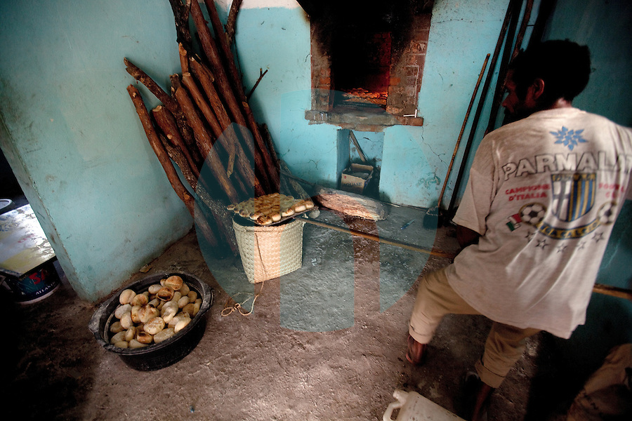 "A man and members of his family bake a local bread roll, known as ""Paun"" in a makeshift bakery in the mountain town of Laclubar, Timor-Leste on Tuesday, Oct. 18th, 2011.  Photographer: Daniel J. Groshong/The Hummingfish Foundation"