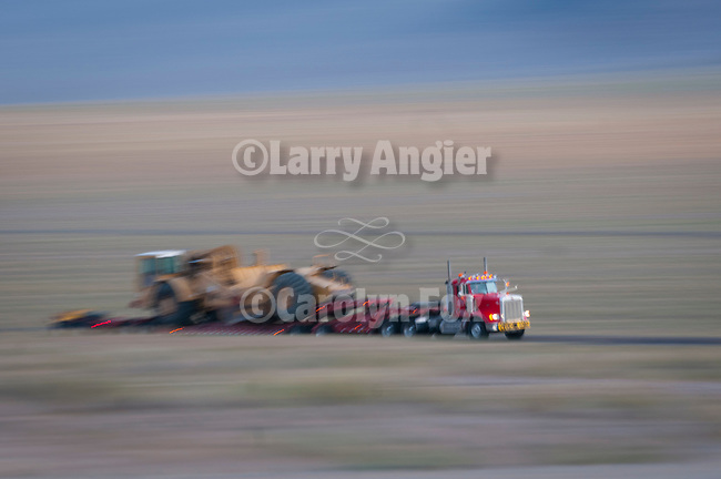 Oversize loaded semi truck and trailer hauls an earth mover on US Highway 95 in Mineral County, Nevada.
