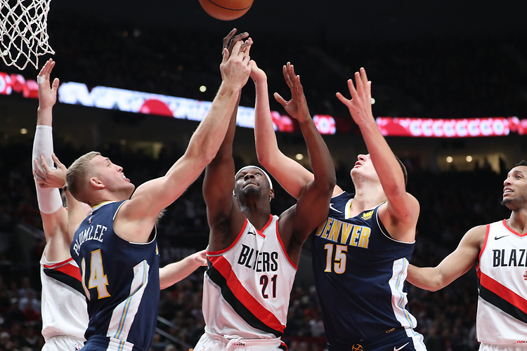 Portland Trail Blazers forward Noah Vonleh (21) goes up for a rebound against Denver Nuggets center Mason Plumlee (24) and Denver Nuggets center Nikola Jokic (15) in the first half at Moda Center.<br /> Photo by Jaime Valdez