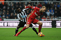 Christian Atsu of Newcastle United battles with Mike van der Hoorn of Swansea City during Newcastle United vs Swansea City, Premier League Football at St. James' Park on 13th January 2018