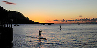 Standup paddlers silhouetted by sunset at Hanalei Bay, Kaua'i.