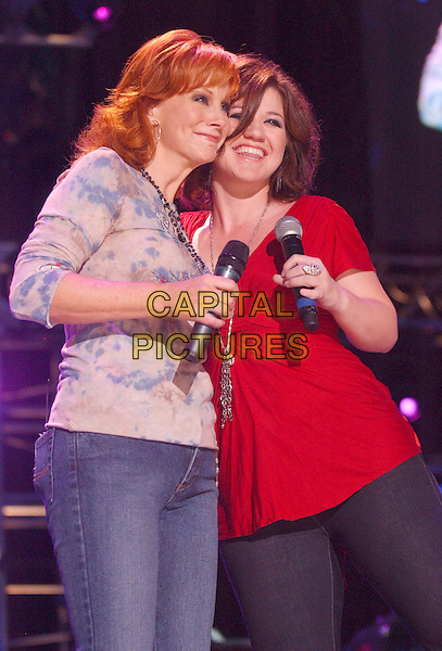 REBA McENTIRE & KELLY CLARKSON.2007 CMA Music Festival held at LP Field, Nashville, Tennessee, USA..June 7th, 2007.half length stage concrt live gig performance music blue top red .CAP/ADM/LF.©Laura Farr/AdMedia/Capital Pictures