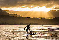 At sunset, a young father teaches his son to surf at Hanalei Bay, Kaua'i.rf.