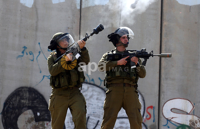 Israeli soldiers standing before the separation wall, protect themselves against teargas during a protest next to the checkpoint of Kalandia, West Bank, 08 March 2012, North of Jerusalem, during a rally to mark the International Women's Day. Photo by Issam Rimawi
