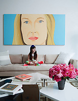 Emma in the family room; the painting is by Alex Katz, and the custom sofa is upholstered in a Castel fabric.