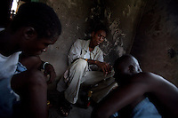 """(from left) Steven, John and Thomas talk  while doing drugs in an abandoned compound   in Monrovia, Liberia on  Wednesday March 21 2007..Melvin, 29 AKA """"Dad"""",  John, 29 AKA """"Desperate Soldier, Thomas 28 AKA """"Bullet Patrol"""", Leroy, 28, AKA """" Pussy Mechanic"""" and Steven 27 AKA """"Field Marshall"""" are all former child soldiers that found each other on the streets after the last round was fired in Liberia. Since then they """"Hustle"""" to put some food in their stomachs and buy some drugs to """" make them forget about their lives""""..ALL NAMES HAVE BEEN FICTIONALIZED TO PROTECT THE IDENTITIES OF THE 5 MEN."""