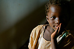 A primary school student in Jinja, Uganda wonders about my camera in a dimly lit classroom