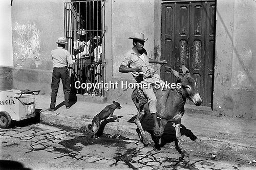 The ice cream seller, and man riding a runaway donkey. San Cristóbal de las Casas, Mexico.  1973