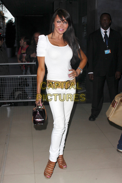 LIZZIE CUNDY.'An Evening At Sanderson' at The Sanderson Hotel, London, England. .April 27th 2010 .full length jeans denim top belt brown beige black bag purse strappy sandals white cleavage lizzy hand on hip.CAP/AH.©Adam Houghton/Capital Pictures.