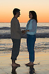 Hispanic couple holding hands, looking at each other at sunset at the beach