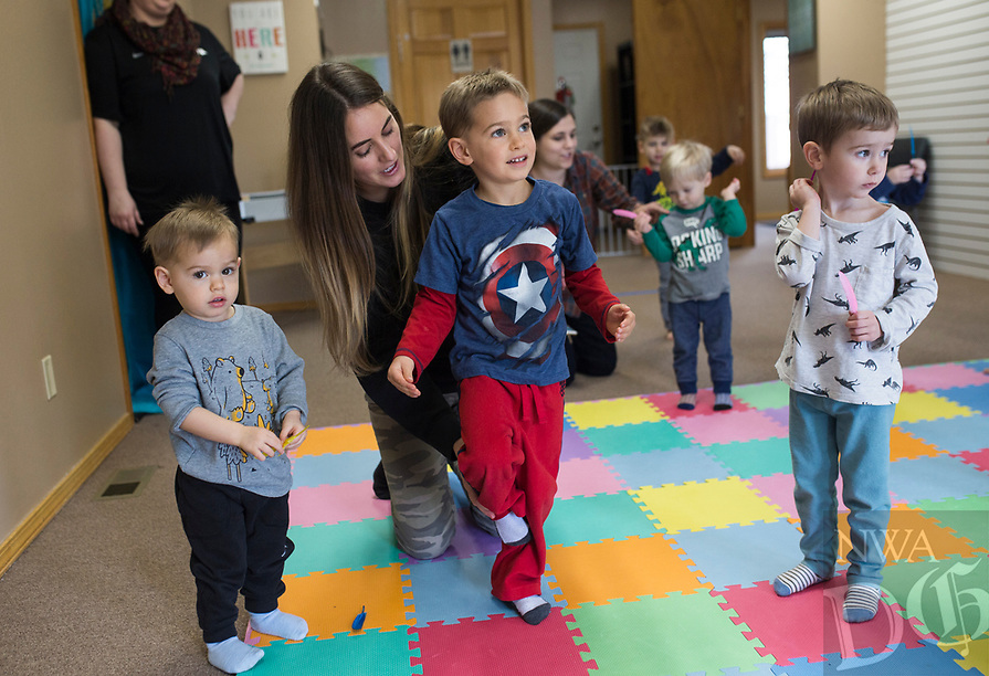 NWA Democrat-Gazette/CHARLIE KAIJO Michelle Combellack of Rogers helps Shane Combellack, 4, with a yoga pose (center) during a Splatter & Stretch class NWA, Thursday, January 10, 2019 at Jubilee Music in Rogers. <br />
