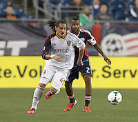 Real Salt Lake forward Devon Sandoval (49) dribbles as New England Revolution defender Andrew Farrell (2) defends. In a Major League Soccer (MLS) match, Real Salt Lake (white)defeated the New England Revolution (blue), 2-1, at Gillette Stadium on May 8, 2013.