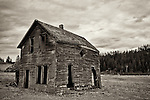 A house sits in decay in a field near a pasture in Idaho.