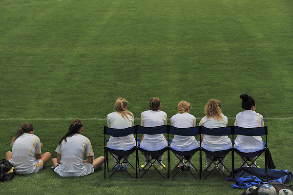 Substitute players sit on the sidelines at a girls soccer game, Denver, Colorado, USA .  John leads private photo tours in Boulder and throughout Colorado. Year-round.