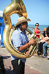 MEXICAN MAN PLAYS the TUBA as he WALKS ALONG SEASIDE