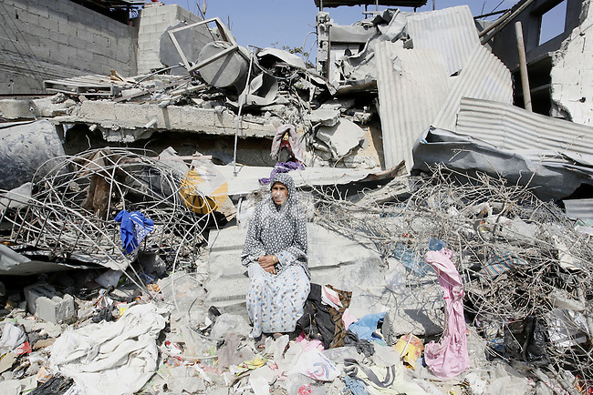 A Palestinian woman sits on the rubble of her house during the visit of Prime Minister Rami Hamdallah to the al-Shijaiyah neighborhood in the east of Gaza city on October 9, 2014. The Palestinian unity government which took the oath of office in June under technocrat prime minister Rami Hamdallah arrived to Gaza Strip on Thursday to convene the first fully meeting. Hamdallah said that the unity government will rebuild the bombed-out Gaza Strip following a seven-week Israeli offensive. Photo by Abed Rahim Khatib