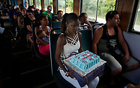ARTEMISA, CUBA - FEBRUARY 15:A Cuban woman carries a cake during a trip Artemisa to Havana, on February 15, 2018 in Cuba. Ferrocarriles de Cuba, is one of the oldest railroad around world, having opened its first route in 1837 with at least 17-mile long. Now the railway probably could cover more than 2,600 miles along the Island. (Photo by Eliana Aponte/VIEWpress)