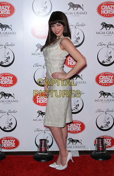 CLAIRE SINCLAIR.Claire Sinclair celebrates her premiere with MGM Grand's Crazy Horse Paris at the MGM Grand Resort Hotel and Casino, Las Vegas, Nevada, USA, .21st October 2010..full length white silver dress hand on hip sleeveless gold  shoes heels side .CAP/ADM/MJT.© MJT/AdMedia/Capital Pictures.