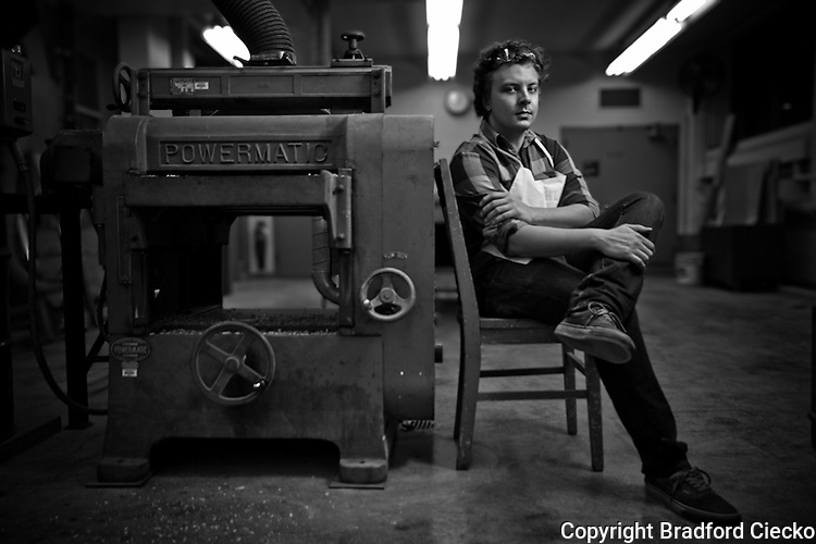 Black and white portrait of a student in a university wood shop next to a large