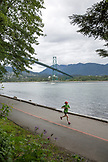 CANADA, Vancouver, British Columbia, a woman runs in front of the Lions Gate Bridge in Stanley Park along the Burrard Inlet