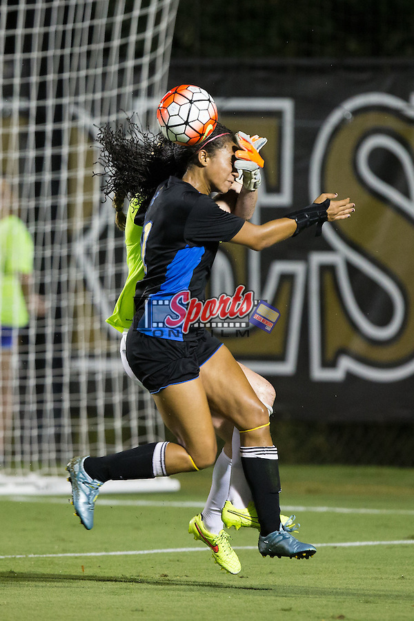 Darian Jenkins (11) of the UCLA Bruins heads the ball away from Lindsay Preston (1) of the Wake Forest Demon Deacons during second half action at Spry Soccer Stadium on September 11, 2015 in Winston-Salem, North Carolina.  The Bruins defeated the Demon Deacons 2-1.  (Brian Westerholt/Sports On Film)