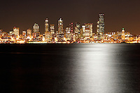 Seattle city skyline at night with light of full moon reflected in Elliot Bay , Seattle, Washington, US