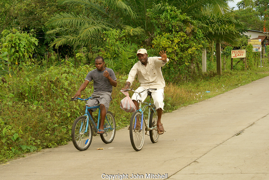 Men riding bicycles in the Garifuna village of Triunfo de la Cruz, Honduras...