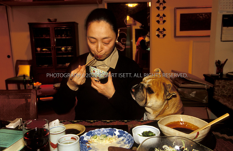 Kyoto, Japan..Mineko Iwasaki at home eating diiner with her pet English bull...All photographs ©2003 Stuart Isett.All rights reserved.