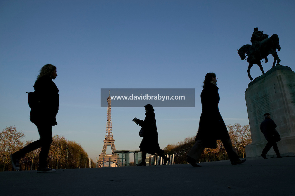 People walk to work near the Eiffel Tower in Paris, France, in the early morning hours of day three of a widespread strike by public sector workers which has paralyzed mass transport in the capital. The strike was called to oppose the government's plans to reform the favored retirement plans of 500,000 government employees.