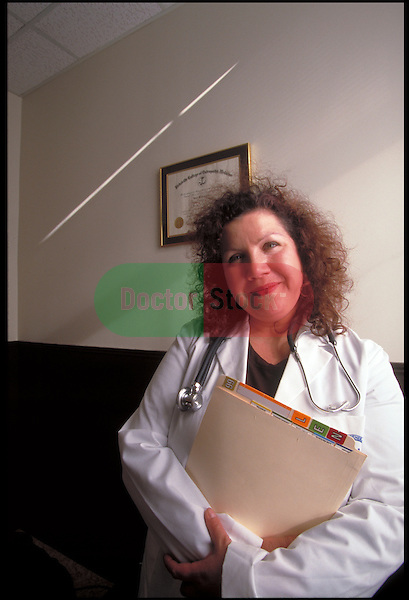 portrait of smiling doctor holding charts