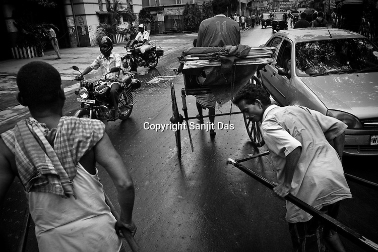 Rickshaw pullers meander through the traffic in Calcutta, India. 93 out of every 100 rickshaw pullers are homeless. They sleep after the city sleeps and wake up before everyone else does. Many of them are the sole bread earners for their family. Many plus 40. Many minus any other specialisation for any other job. Of the twenty four thousand rickshaw pullers, only 387 have licenses. .Many rickshaw pullers earn a meagre wage of 100-150 rupees (US $ 2.25-3.5) a day of which they have to give a daily rickshaw rent of 60 (US$ 1.35) rupees to the agent at the end of the day.