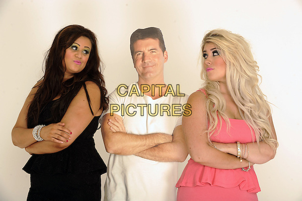 '2 Shoes' duo Lucy Texeira & Charley Bird, London, .August 30th, 2012.**Exclusive. Double fees apply.**.studio x factor half length black pink peplum dress Simon Cowell cardboard cutout arms crossed white t-shirt .CAP/FIN.©Steve Finn/Capital Pictures.