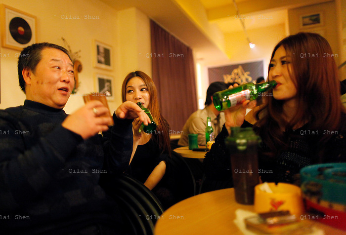"""Patrons drink at Tony's Bar in Nanjing, China on 04 March, 2011.  Once a mid level executive at a state owned chemical company, Mr. Tony Zhao started the bar for a more interesting life and make """"connections"""" for future business opportunities."""