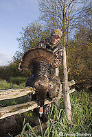 Hunter displaying wild turkey over wooden fence