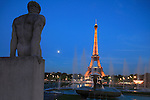 The twilight view of a statue and fountains in Jardins Trocadero with Eiffel Tower in the background.City of Paris. Paris. France