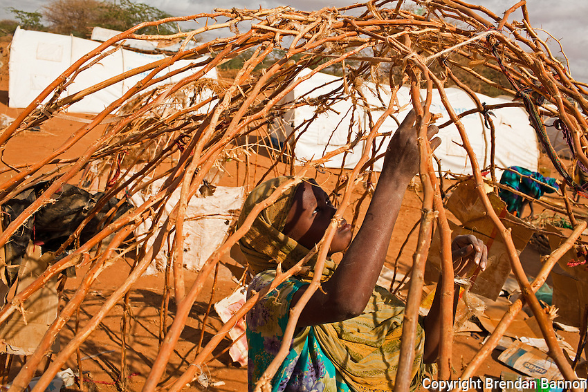 20 year old Somali refugee Nula Abdi dismantling her makeshift shelter in Ifo camp in Dadaab, the world's largest refugee camp in Kenya.