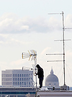 Un uomo sistema delle antenne su un palazzo condominiale, a Roma, 26 novembre 2013. Sullo sfondo, il Palazzo della Civilta' Italiana, a destra, e la Basilica dei Santi Pietro e Paolo, all'EUR.<br /> A man adjusts tv aerials on a resident's terrace in Rome, 26 November 2013. In background, the Palazzo della Civilta' Italiana (also known as the Square Colosseum), left, and the Saints Peter and Paul's Basilica, at the EUR residential and business district.<br /> UPDATE IMAGES PRESS/Riccardo De Luca