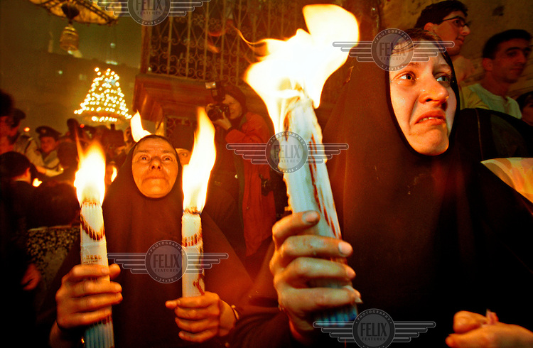 Christian nuns hold lit torches in the Church of the Holy Sepulchre on Good Friday.