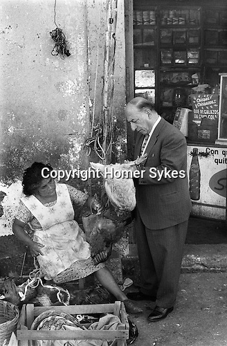 Oaxaca food shopping.  man checking if a chicken he is perhaps going to buy is plump. 1973