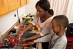Mother in kitchen with 10 year old son, food preparation, boy peeling raw carrot as mother washes sweet red pepper strips