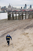 A man uses a metal detector at low tide on the south bank of the River Thames, London.