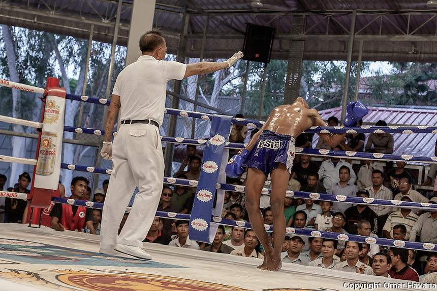 SIEM REAP, CAMBODIA. A referee counts to ten to one of the fighters after he received an elbow from his opponent during a fight in the Siem Reap arena in Cambodia. Pradal Serey or Kun Khmer -free fighting- is an unarmed martial art from Cambodia. Compared to other forms of Southeast Asian kickboxing, Kun Khmer emphasises more elusive and shifty fighting stances. The Cambodian style tends to utilise more elbows than that of other regions. Evidence shows that a style resembling pradal serey existed in the 9th century, leading the Khmer to believe all Southeast Asian forms of kickboxing started with the early Mon-Khmer people. They maintain that Pradal Serey has influenced much of the basis of Muay Thai. During the Khmer Rouge genocide, traditional martial arts were banned and many boxers were executed or worked to death, which nearly caused the death of pradal serey. Nowadays, Kun Khmer is making a strong comeback in Cambodia, with fighters attempting to market their style of boxing at the same caliber of Muay Thai. Photography: ©Omar Havana