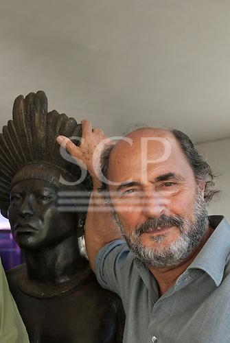 Brasilia, Brazil. Sidney Possuelo, Indigenist  with bust of an Indigenous man. Memorial dos Povos Indigenas Museum.