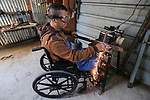 Palestinian blacksmith Jalal Abu Hayah (40), on Wheelchair-bound who became disabled during the clashes with Israeli troops along the Israel-Gaza border, makes swords and daggers, at his workshop, in Khan Younis in the southern Gaza Strip on January 16, 2020. Photo by Ashraf Amra